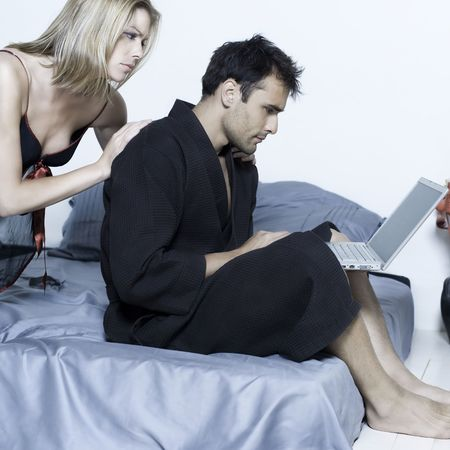 jealousy: beautiful young caucasian couple in a bed on isolated background with computer laptop