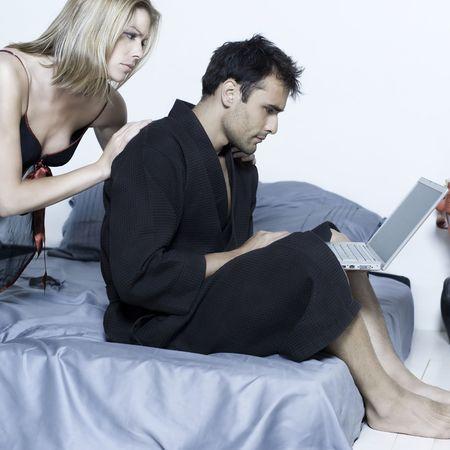 celos: caucasian joven y bella pareja en la cama en un aislado fondo con ordenador port�til
