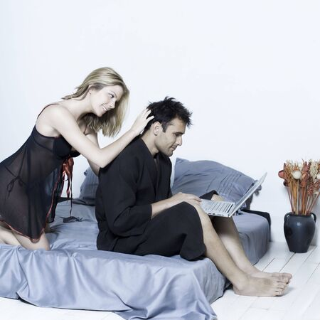 beautiful young caucasian couple in a bed on isolated background with computer laptop Stock Photo - 3540536