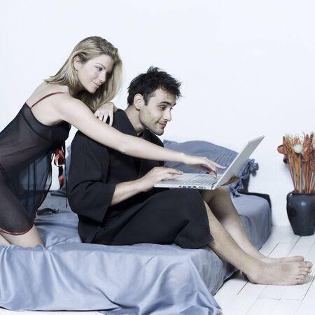 caucasian joven y bella pareja en la cama en un aislado fondo con ordenador portátil Foto de archivo - 3540548