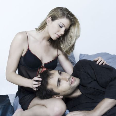 cuddles: beautiful young caucasian couple in a bed on isolated background