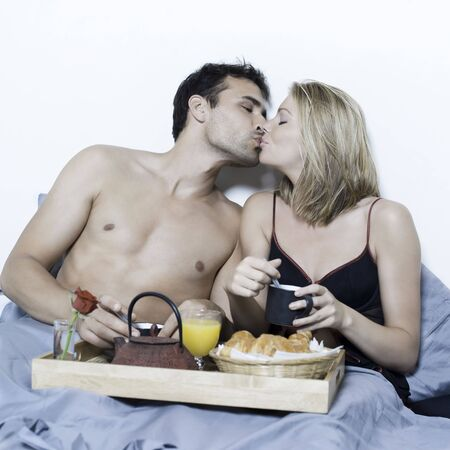 desayuno romantico: caucasian joven y bella pareja en una cama de tener antecedentes aislados en la cama breafast