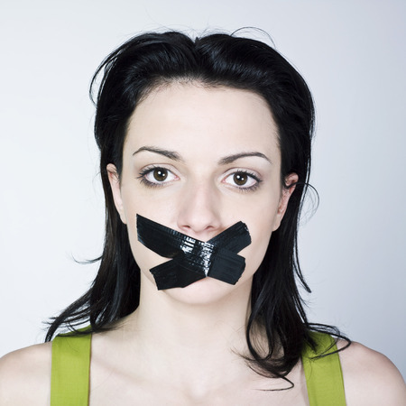 stifle: portrait of young woman reduce to silence on isolated background