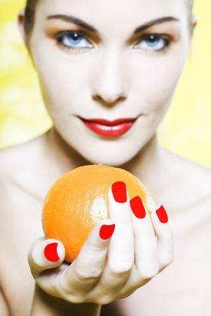 beautiful woman portrait with colorful make-up  and background holding a mandarine Stock Photo - 3999381