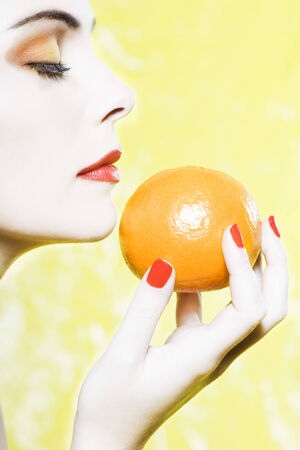 beautiful woman portrait with colorful make-up  and background holding a mandarine Stock Photo - 3999443
