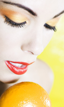 beautiful woman portrait with colorful make-up  and background holding a mandarine Stock Photo - 3999483