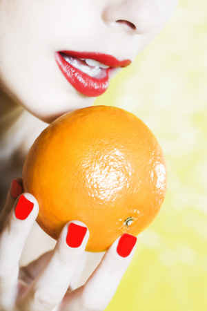 beautiful woman portrait with colorful make-up  and background holding a mandarine Stock Photo - 3975585