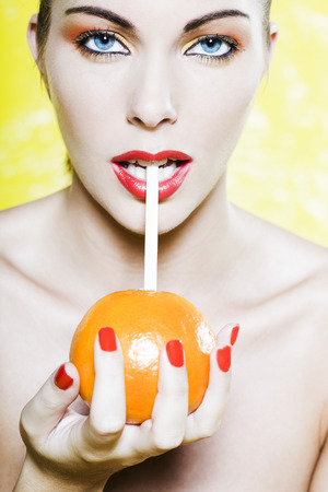 beautiful woman portrait with colorful make-up  and background drinking orange juce with straw Stock Photo - 3999479