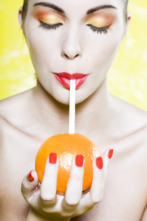 beautiful woman portrait with colorful make-up  and background drinking orange juce with straw Stock Photo - 3999458