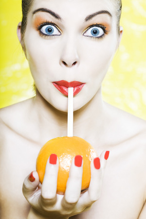 beautiful woman portrait with colorful make-up  and background drinking orange juce with straw Stock Photo - 3999418