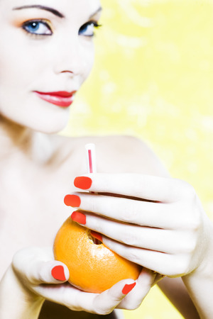beautiful woman portrait with colorful make-up  and background holding a mandarine Stock Photo - 3999364