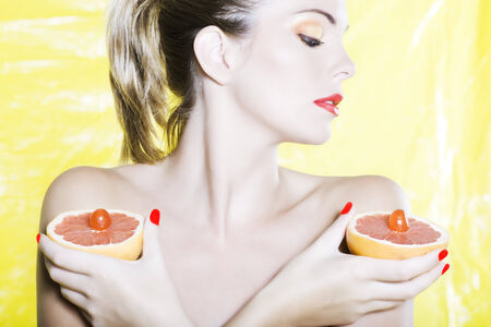 beautiful woman portrait with colorful make-up  and background holding grapefruit Stock Photo - 3999464