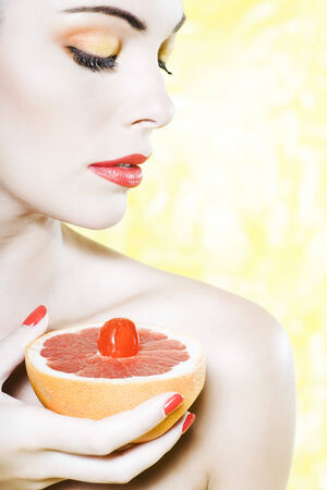 beautiful woman portrait with colorful make-up  and background holding grapefruit Stock Photo - 3999406