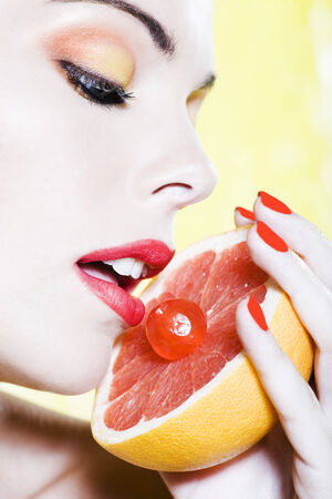 beautiful woman portrait with colorful make-up  and background holding grapefruit Stock Photo - 3999608
