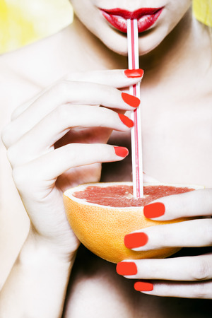 beautiful woman portrait with colorful make-up  and background drinking grapefruit juice with straw Stock Photo - 3975577