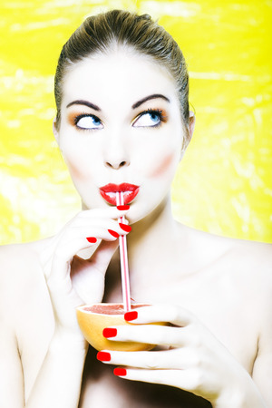 beautiful woman portrait with colorful make-up  and background drinking grapefruit juice with straw Stock Photo - 3999487