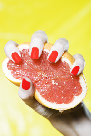 woman hand with red nails and colorful background squeezing grapefruit Stock Photo - 3975591