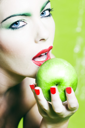 beautiful woman portrait with colorful make-up  and background holding apple Stock Photo - 3999476