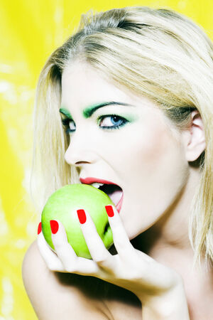 beautiful woman portrait with colorful make-up  and background biting apple Stock Photo - 3999808