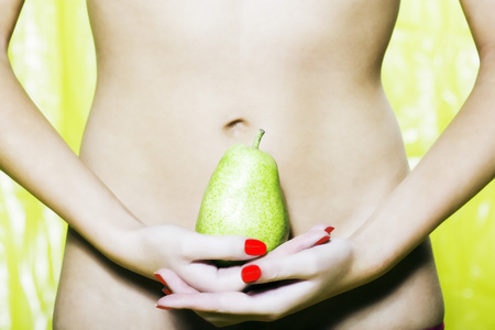 digestion: beautiful woman portrait with colorful make-up  and background holding pear