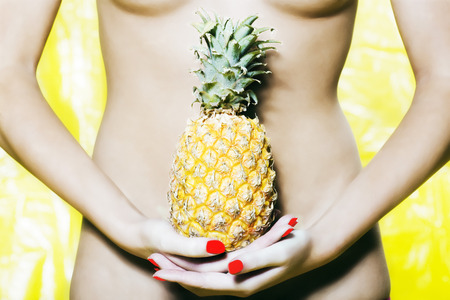 digestion: beautiful woman portrait with colorful make-up  and background holding pineapple LANG_EVOIMAGES