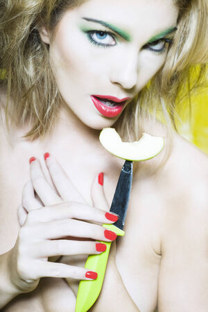 beautiful woman portrait with colorful make-up  and background holding apple slice on knife Stock Photo - 3999573