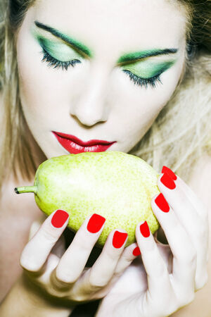 beautiful woman portrait with colorful make-up  and background holding pear Stock Photo - 3999554