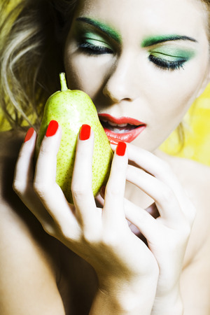 beautiful woman portrait with colorful make-up  and background holding pear Stock Photo - 3999424