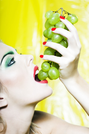 beautiful woman portrait with colorful make-up  and background eating grape Stock Photo - 3999534
