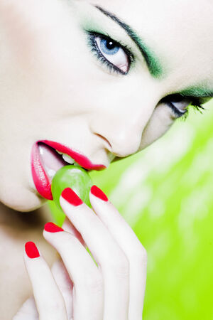 beautiful woman portrait with colorful make-up  and background holding grape Stock Photo - 3999451