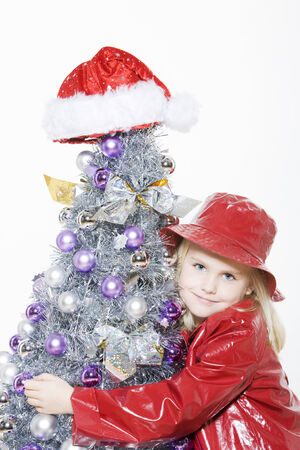 indoors picture of a little girl preparing christmas tree on isolated white background Stock Photo - 3999738
