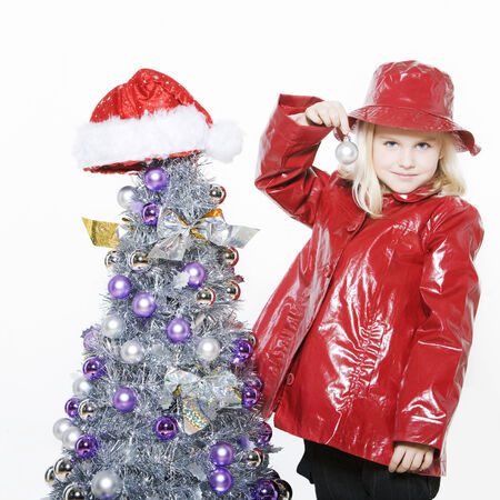 indoors picture of a little girl preparing christmas tree on isolated white background Stock Photo - 3999734
