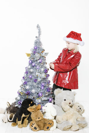 indoors picture of a little girl preparing christmas tree on isolated white background Stock Photo - 4006748