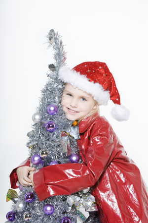 indoors picture of a little girl preparing christmas tree on isolated white background Stock Photo - 3999758