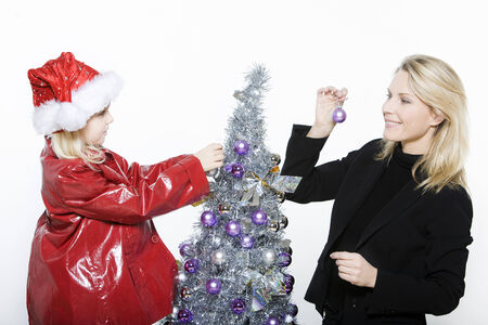 indoors picture of a little girl with her mother preparing christmas tree on isolated white background Stock Photo - 3999816