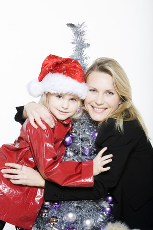 indoors picture of a little girl with her mother preparing christmas tree on isolated white background Stock Photo - 3999768