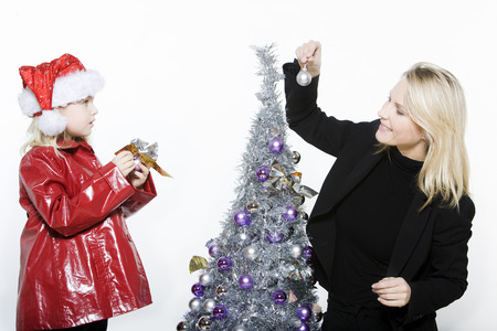 indoors picture of a little girl with her mother preparing christmas tree on isolated white background Stock Photo - 3999815