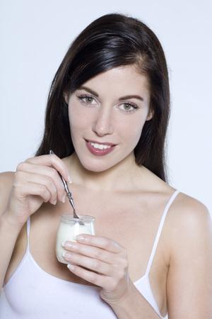beautiful young woman on isolated background eating yogourt photo