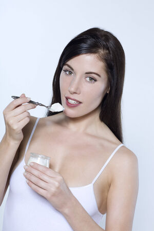 beautiful young woman on isolated background eating yogourt photo