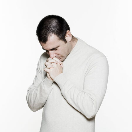 man praying: Portrait of an handsome expressive man in studio on white isolated background