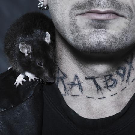 punk: portrait en studio sur fond isol� d'un homme �trange avec son rat