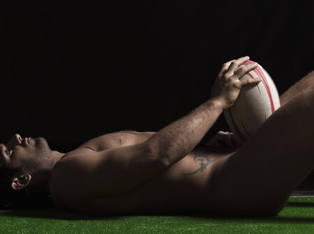 Side profile of naked young man lying with a rugby ball Stock Photo - 5988108