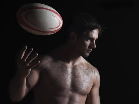 Close-up of a naked young man tossing a rugby ball Stock Photo - 5988045