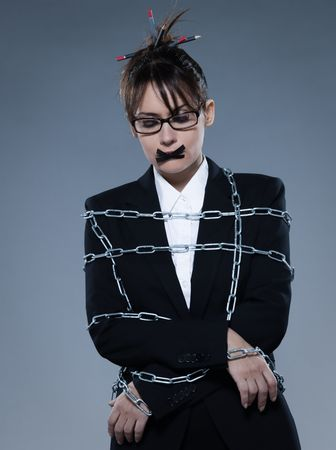 overwork: beautiful business woman chained on isolated background