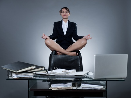 levitate: beautiful cheerful caucasian  business woman levitate from her desk on isolated background