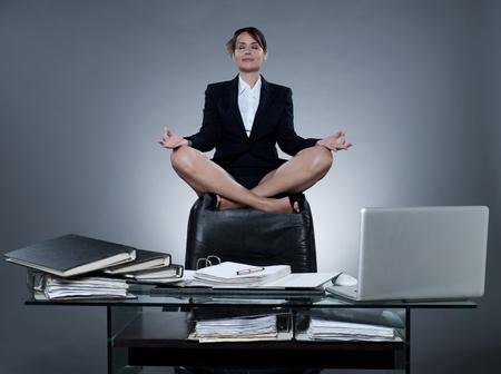 mujer de negocios caucásica alegre hermosa levitar desde su escritorio en fondo aislado