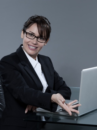 beautiful cheerful caucasian  business woman sitting at desk on isolated background Stock Photo - 9823617