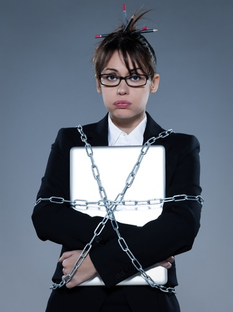 stifle: beautiful business woman on isolated bacground chained to  her laptop LANG_EVOIMAGES