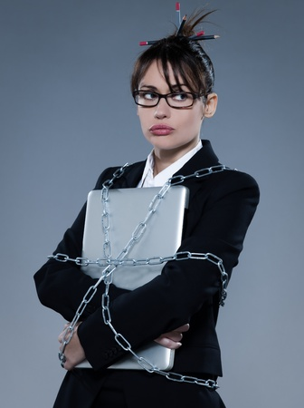 exasperate: beautiful business woman on isolated bacground chained to  her laptop LANG_EVOIMAGES
