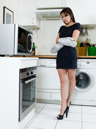 in oven: beautiful caucasian woman in a kitchen waiting with anxiety in front of the oven